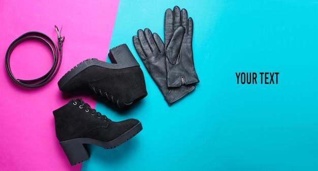 분홍색 파란색 배경에 유행 여성 신발 및 액세서리의 미니멀리즘 콜라주. 검은 부츠, 가죽 장갑, 벨트. 공간을 복사하십시오. 평면도