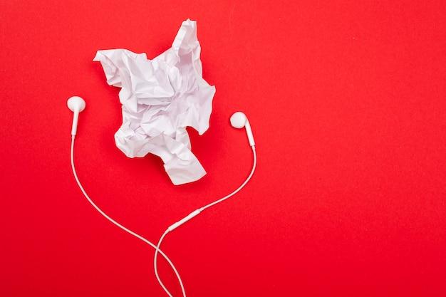 ミニマリズムのコンセプトです。空白の赤い壁にヘッドフォンで紙を丸めてシート