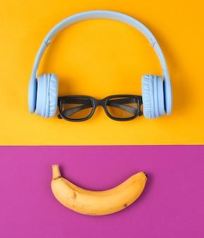 헤드폰, 안경 및 바나나로 웃는 얼굴의 미니멀리즘 평면 누워 개념