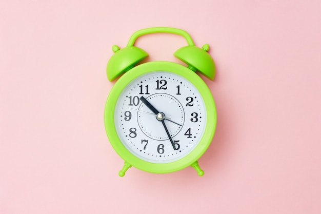 Minimalism green alarm clock on a pink background