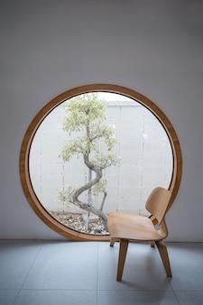 둥근 창문과 안뜰에 나무가있는 나무 의자의 미니멀리즘 인테리어