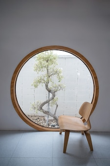 Minimalism interior of wooden chair with round window and tree at patio