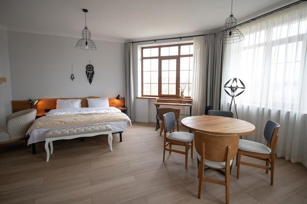 ミニマリズム。大きな窓、ベッド、椅子付きの丸い木製テーブルのある広々としたリビングルーム