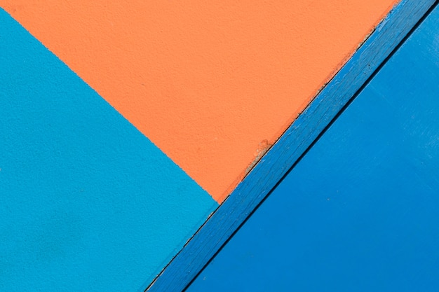 Minimalism style, blue and orange wall texture background and blue door, rotate side.
