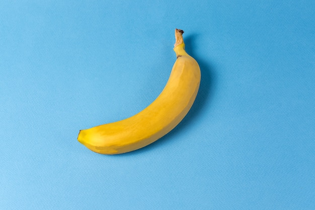 Minimalism style. fruit pattern with yellow banana over blue background.