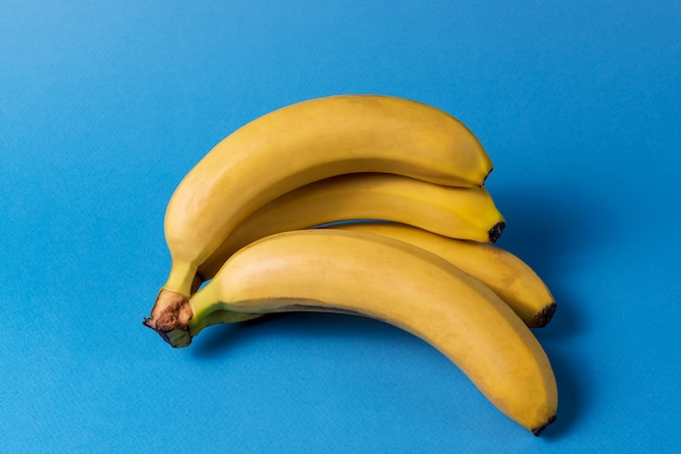 Minimalism style. pattern with bunch of yellow ripe banana fruit over blue background.