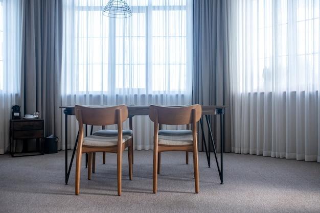ミニマリズム。日中はカーテン付きの大きな窓のある部屋の中央にあるカーペットの上に椅子が置かれたテーブル
