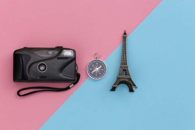 ミニマリズム旅行、冒険フラットレイ。カメラとコンパス、青ピンクのパステルカラーの背景にエッフェル塔の置物。上面図