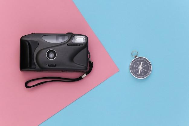 미니멀리즘 여행, 모험 플랫 레이. 블루 핑크 파스텔 배경에 카메라와 나침반. 평면도