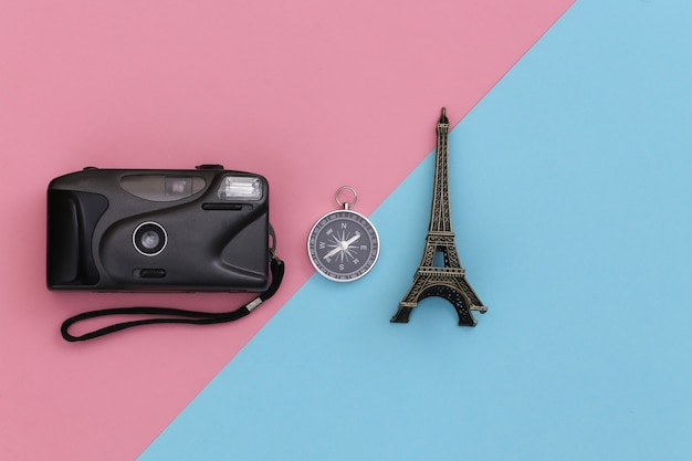 Minimalism travel, adventure flat lay. camera and compass, eiffel tower figurine on a blue-pink pastel background. top view
