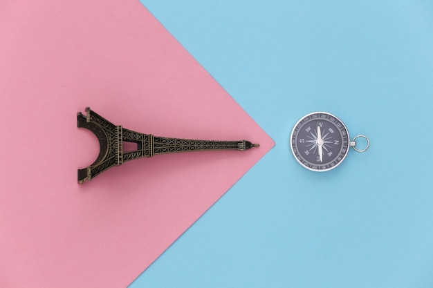 Minimalism travel, adventure flat lay. camera and eiffel tower figurine on a blue-pink pastel background. top view
