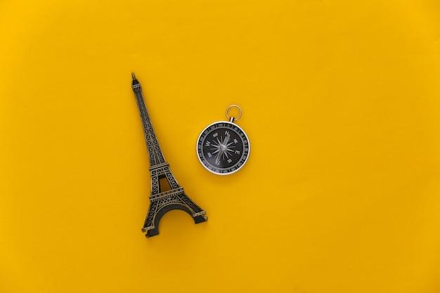 ミニマリズム旅行、冒険フラットレイ。黄色の背景にコンパスとエッフェル塔の置物。上面図