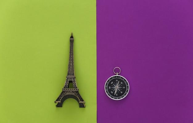 ミニマリズム旅行、冒険フラットレイ。紫緑色の背景にコンパスとエッフェル塔の置物。上面図