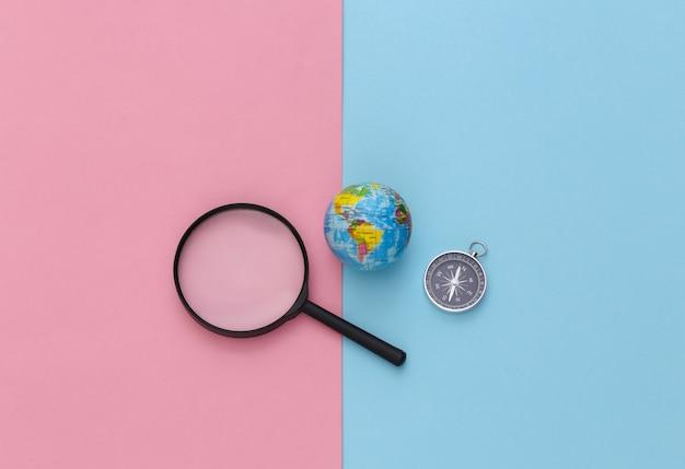 Минимализм путешествия, приключенческая планировка квартиры. компас и лупа, глобус на сине-розовом пастельном фоне. вид сверху.