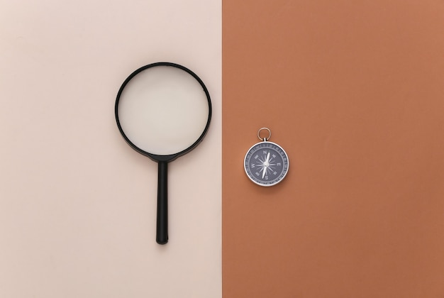 Минимализм путешествия, приключенческая планировка квартиры. компас и лупа на коричневом бежевом фоне. вид сверху