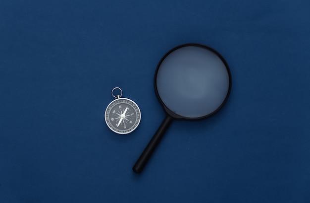 Минимализм путешествия, приключенческая планировка квартиры. компас и лупа на классическом синем фоне. вид сверху