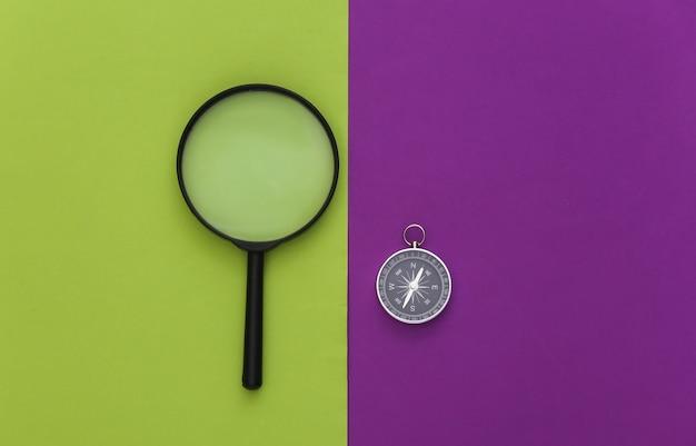 Минимализм путешествия, приключенческая планировка квартиры. компас и лупа на фиолетовом зеленом фоне. вид сверху