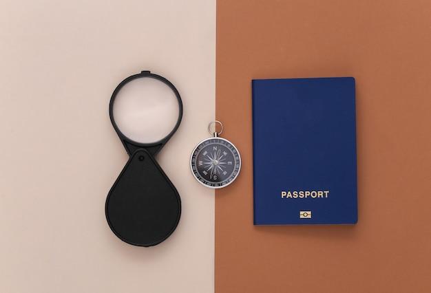 Минимализм путешествия, приключенческая планировка квартиры. компас и лупа, паспорт на коричнево-бежевом фоне. вид сверху