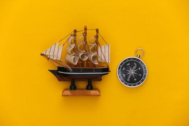 미니멀리즘 여행, 모험 플랫 레이. 노란색 배경에 나침반과 배입니다. 평면도