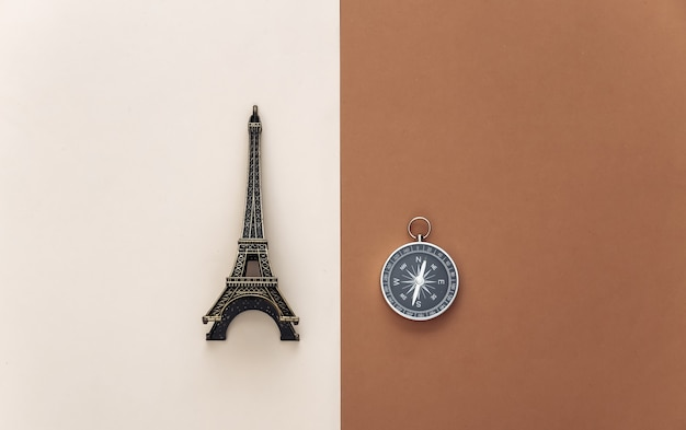 Minimalism travel, adventure flat lay. compass and eiffel tower figurine on beige brown background. top view