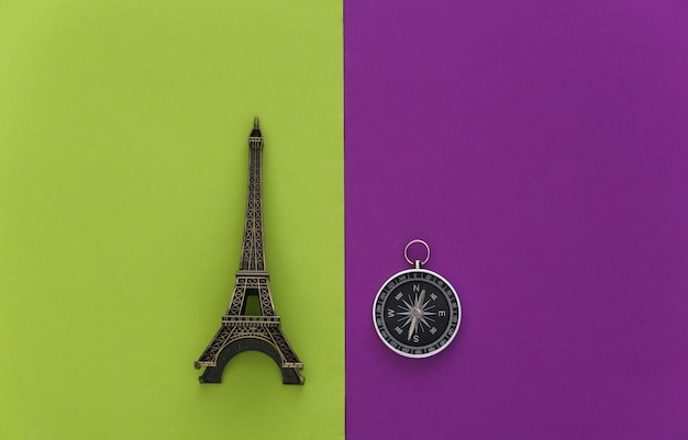 Minimalism travel, adventure flat lay. compass and eiffel tower figurine on purple green background. top view