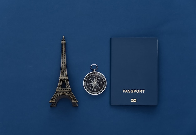 Minimalism travel, adventure flat lay. compass, passport and eiffel tower figurine on classic blue background. top view