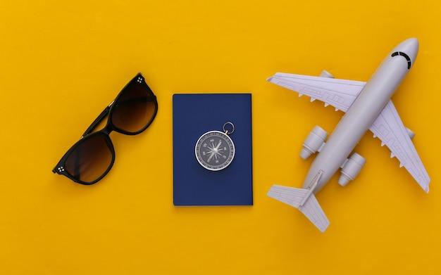 미니멀리즘 여행, 모험 플랫 레이. 노란색 배경에 나침반, 여권, 선글라스, 비행기. 평면도