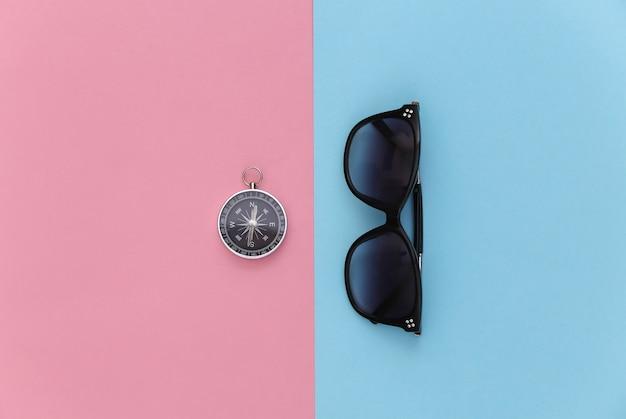 미니멀리즘 여행, 모험 플랫 레이. 블루 핑크 파스텔 배경에 선글라스와 나침반. 평면도