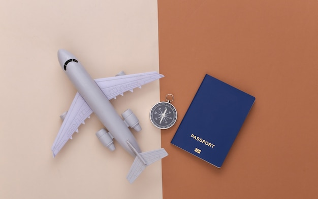 미니멀리즘 여행 플랫 레이. 베이지색 갈색 배경에 나침반과 비행기입니다. 평면도