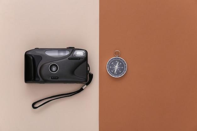 미니멀리즘 여행 플랫 레이. 베이지색 갈색 배경에 나침반과 카메라입니다. 평면도