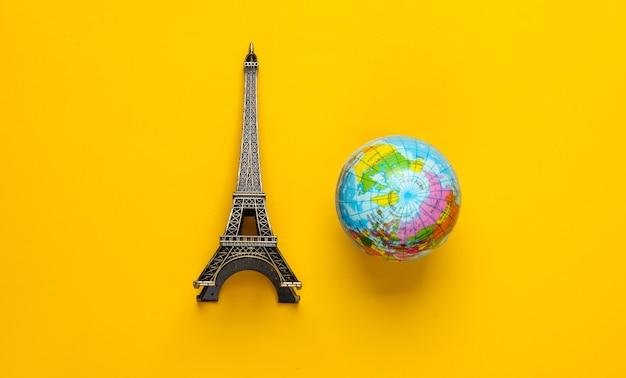 미니멀리즘 여행 정물. 노란색에 지구본, 에펠 탑의 입상