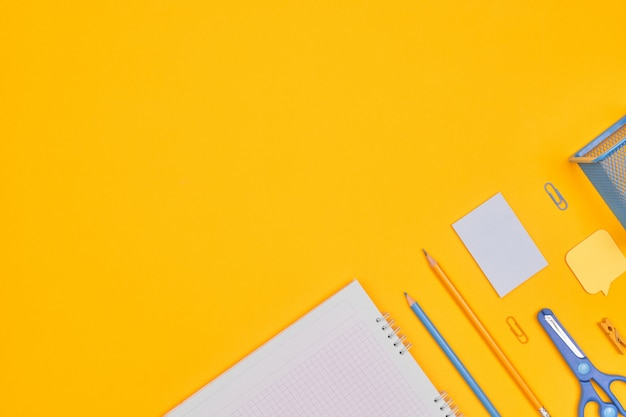 Минимализм желто-синие канцелярские товары на желтом фоне