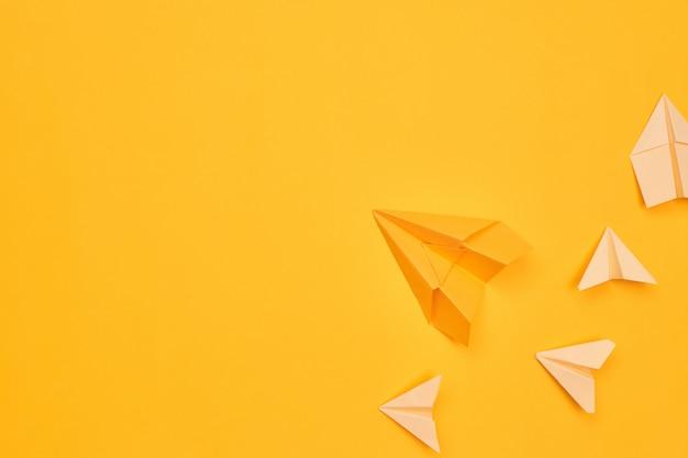 노란색 배경에 미니멀리즘 노란색 종이 비행기