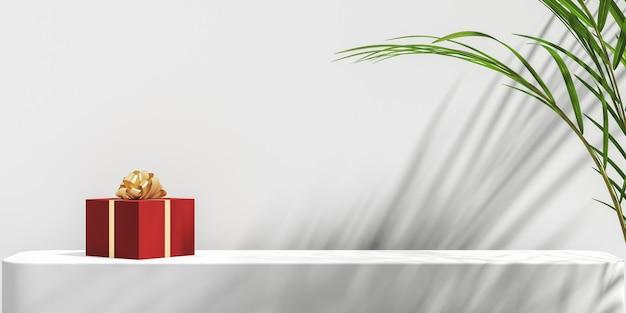ミニマリストの抽象的なモックアップの背景、白いプラットフォーム上の赤いギフトボックス、白い壁にサンシェード熱帯植物の影、熱帯植物の前景。 3dレンダリング