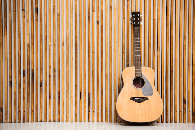 Minimalist acoustic guitar on wooden background