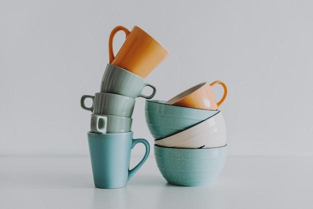 Минималистичная и абстрактная композиция с чашками и глубокими тарелками.