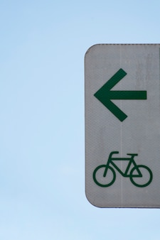 Minimalist arrow sign for bicycles and sky
