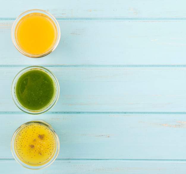 Minimalist assortment of fresh smoothies on wooden background