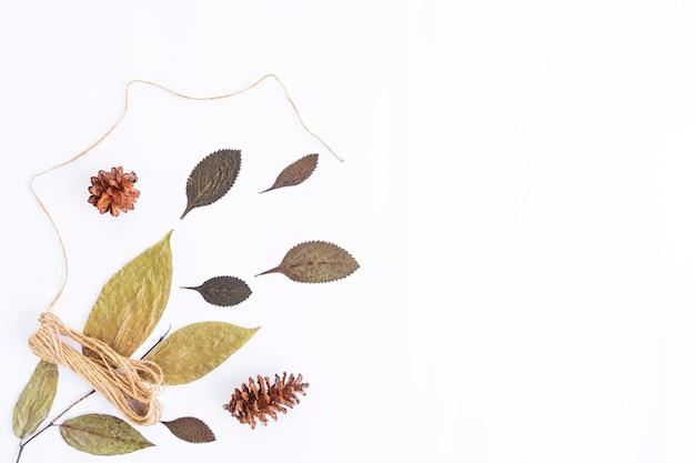 미니멀한 가을 컨셉입니다. 말린 잎, 흰 종이 배경에 고립 된 삼 베 원사