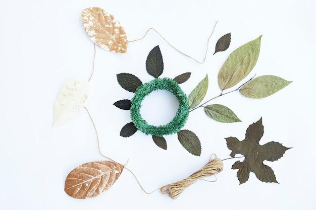 미니멀한 가을 컨셉입니다. 말린 잎, 소나무 꽃, 크랜스 화환, 삼베 원사 흰 종이 배경에 고립