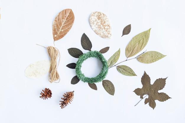 ミニマリストの秋のコンセプト。乾燥した葉、松の花、クランリース、白い紙の背景に分離された黄麻布の糸