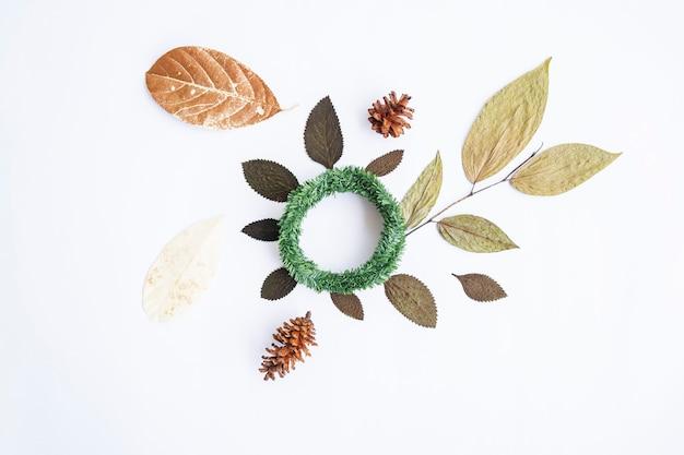 미니멀한 가을 컨셉입니다. 말린 잎, 소나무 꽃, 흰 종이 배경에 고립 된 크랜 화환