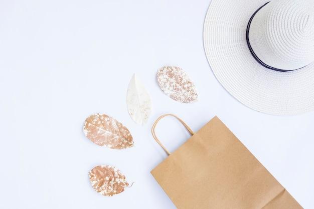 ミニマリストの秋のコンセプト。ホワイトペーパーの背景に分離された乾燥葉ホワイトハット紙袋