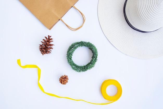 ミニマリストの秋のコンセプト。紙袋、白い帽子、リボンロープ、松の花、白い紙の背景に分離されたクランの花輪。ミニマリストのクリスマスのコンセプト