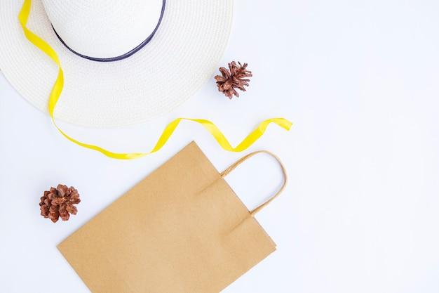 미니멀한 가을 컨셉입니다. 종이 가방, 흰 모자, 리본 문자열 흰 종이 배경에 고립