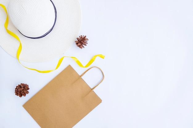 ミニマリストの秋のコンセプト。紙袋、白い帽子、白い紙の背景に分離されたリボンの文字列