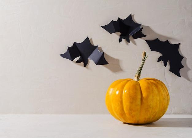 할로윈의 미니멀한 배경입니다. 주황색 호박과 베이지색 배경에 장식용 검은 박쥐, 텍스트 복사