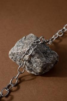 天然素材とミニマリストベージュブラウンife組成物:石と鋼のチェーン、抽象的な現代アートデザインコンセプト側面図