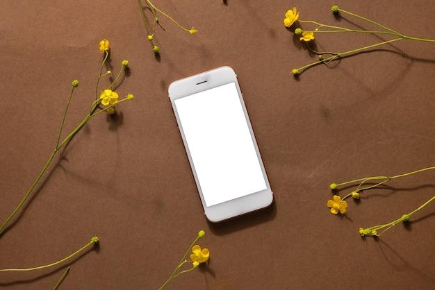 ワイルドフラワーとテクノロジーを備えたミニマリストベージュブラウンの生命構成-携帯電話、黄色い花、抽象的な現代アートデザインコンセプト上面図