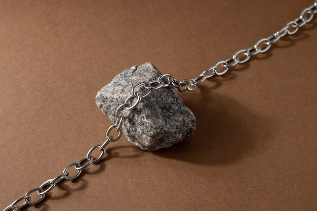 天然素材のミニマリストベージュブラウン静物構成:石と鋼のチェーン、抽象的な現代アートデザインコンセプト側面図